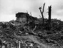 Heavily laden soldiers trudge through mud past the shattered remains of a concrete structure. Around them broken trees, steel beams and other pieces of debris have been strewn.