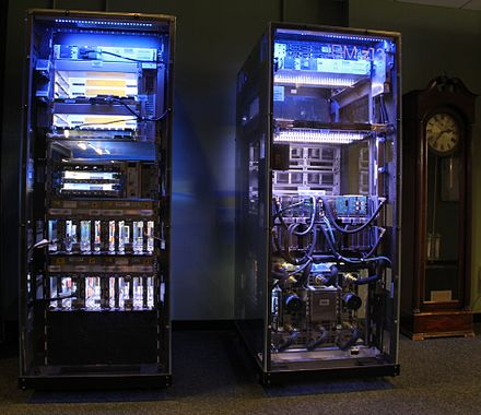 An IBM z13 with the cover removed. The interior is lit to better see the various internal parts. Glowing IBM z13 and clock - cropped.JPG