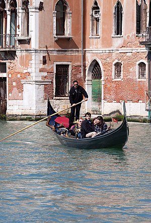 A gondola with tourists in Venice, Italy.