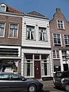 foto van Huis met schilddak en gebosseerd grijsgepleisterde lijstgevel met sierankers. Winkel
