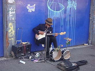 One-man band - A musician in London performs on electric guitar and a small drum kit.