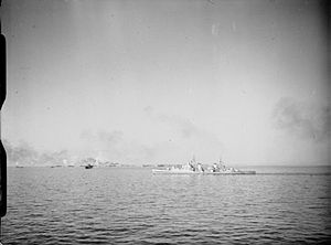 HMS Spartan (95) - Spartan bombarding enemy shore positions as the landing craft of the U.S. 5th Army close in on the beaches in the opening stages in the battle for Rome. Smoke can be seen rising from the beachhead.