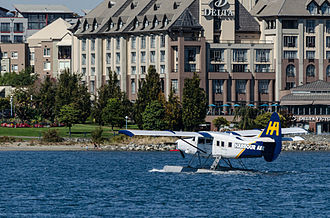 Victoria Inner Harbour Airport - A Harbour Air plane taxiing into Victoria Harbour in front of the Delta Victoria