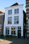 foto van Huis met gebosseerd gepleisterde lijstgevel, schilddak met rode pannen belegd