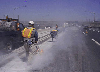 Concrete saw - Highway road workers using concrete saws and generating dust.