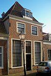 foto van Eenvoudige laat 18e- begin 19e-eeuwse gevel voor pand met hoge kap; roeden in de vensters