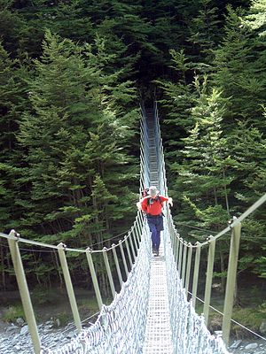 Tramping in New Zealand - A tramper crossing a swingbridge over the Huxley River in the South Island of New Zealand.
