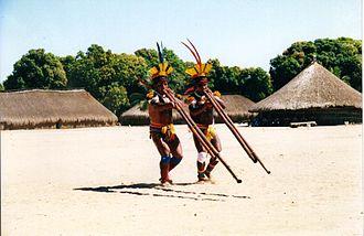 Xingu Indigenous Park - Pátio da Aldeia Kamaiurá, Alto-Xingu. Indigenous people playing the uruá flute