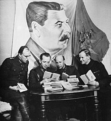 Four Finnish officers in uniform are sitting and reading Soviet skiing manuals with relaxed looks on their faces. A pile of the books is in front of them on a table while a large drape of Joseph Stalin hangs above their heads on the wall.