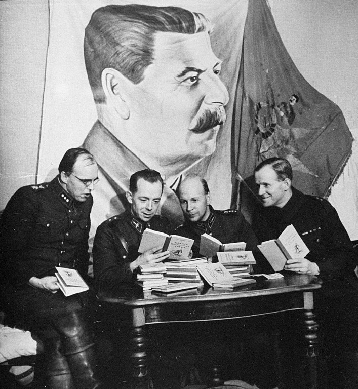 Finnish officers inspecting Soviet skiing manuals during the Winter War, February 1940. Behind them are Stalin banners captured in battle. [707 x 768]