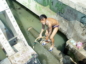 Child poverty - A boy bathes in a polluted river in Jakarta, Indonesia.