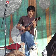 Shimabukuro seated and playing ukelele