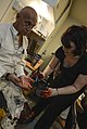 Jenny Bucklant, right, a makeup artist with Amputees in Action, applies makeup and a prosthetic leg to Pet Thomas, an actor with Amputees in Action, during a mass casualty medical drill May 19, 2013, as part 130519-N-OM642-159.jpg