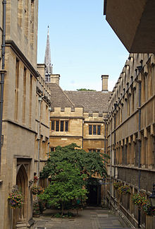 A narrow courtyard, longer than it is wide; a tree at the far end and hanging baskets of flowers on each side; tall stone buildings on each side, the ones at the far end topped with crenellations; a large archway on the left; above roof-level, a tall metal spire