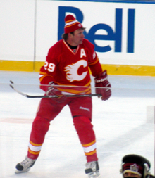 "A hockey player in a red uniform with white and yellow trim and a stylized ""C"" logo on his chest skates forward as he looks to his left."