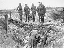 Cinq hommes en uniformes sur le parapet d'une tranchée