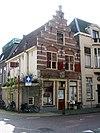foto van Hoekhuis met trapgevel met speklagen en door pinakel op gebeeldhouwd kraagsteentje bekroond