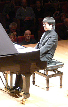 A Chinese man sits at piano, performing, while an audience watches.