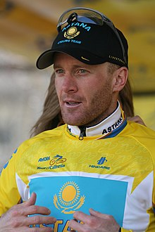 A bearded man in his mid-thirties stands in front of a partly visible woman who is zipping up the back of his yellow cycling jersey. He wears a black baseball cap with sunglasses on the cap.