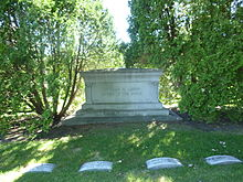 "Large monument between two trees, inscribed ""Charles M. Loring/Father of the Parks"". Loring's grave is center left of four visible."