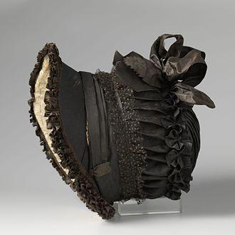 Poke bonnet - A black silk poke bonnet, trimmed with velvet and tulle from circa 1815