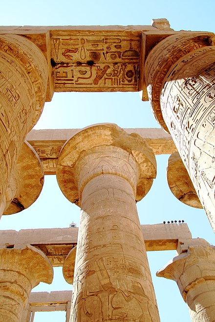 Example of the inscriptions present throughout the complex. As visible from this image, the upper regions are painted, suggesting (in cannon with other such temples) that the remain columns and ceilings would have been brightly painted. The temple roof representing the heavens would often display images of stars and birds, whereas the columns often boast images of palm plants, lotus and people. Luxor Karnak-Tempel 2016-03-21 Grosse Saulenhalle 04.jpg