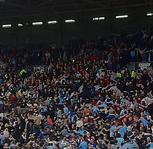 Photo des supporters de Manchester City, en tribune dos tourné au terrain, effectuant la danse du Poznań.