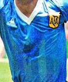 Photographie en couleurs. Gros plan sur l'écusson contrefait de la fédération argentine de football cousu sur un maillot bleu plus foncé.