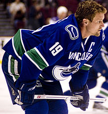A Caucasian ice hockey player in his mid-thirties. He stands crouched over on the ice with his stick rested horizontally on his knees. He wears a blue jersey with white and green trim and is helmetless.