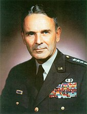 Middle-aged man with graying dark hair parted slightly off-center. He wears a green dress uniform, with suit and tie, is clean-shaven, and has four stars on his shoulder to indicate his rank.