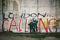 Meme artist XVALA with hand gesture, standing near graffiti artist Banksy's Steve Jobs Mural in Calais, France 2017.jpg