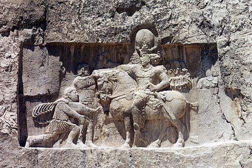 Rock-face relief at Naqsh-e Rustam of Iranian emperor Shapur I (on horseback) capturing Roman emperor Valerian (kneeing) and Philip the Arab (standing). Naqsh i Rustam. Shapour.jpg