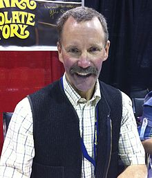 The bust of a middle-aged caucasoid man looking to the photographer's left; he is wearing spectacles and a yellow-plaid collared shirt under a cardigan sweater.
