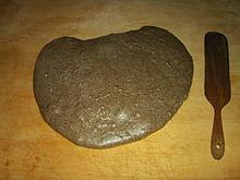 Polenta taragna sulla tavola di legno e coltella di legno