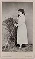 Porträttfoto i ateljé, en kvinna som håller på att räfsa - Nordiska Museet - NMA.0039745.jpg