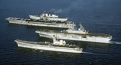 Four aircraft carriers, Principe-de-Asturias, USS Wasp, USS Forrestal  and HMS Invincible (front-to-back), showing the difference in size between a supercarrier, light V/STOL carriers, and an amphibious carrier.