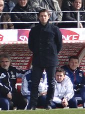 A photograph of Rémi Garde, standing in the managerial dugout.