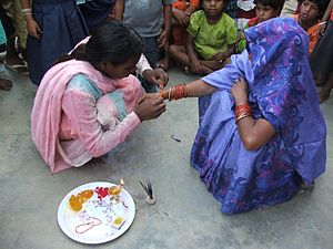 Raksha Bandhan - A girl is tying a rakhi (a Rakshasutra) around her mother's wrist as part of the celebration Rakshbandhan in a village Lahree,  Jabalpur district, Madhya Pradesh, India.