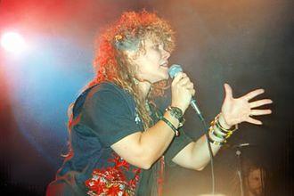Resurrection Band - Wendi Kaiser, lead singer of Resurrection Band, with husband/guitarist/lead singer Glenn Kaiser in the background.