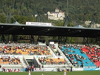 FC Vaduz - Main stand of the Rheinpark Stadion with Vaduz Castle in the background.