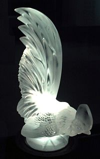 Illuminated automobile hood ornament in the form of a rooster
