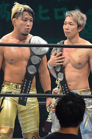 IWGP Junior Heavyweight Tag Team Championship - Sho (left) and Yoh (right), Roppongi 3K, with the title belts in November 2017