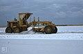 Salt grader ploughs a swathe across field, white for harvest. Inagua (38155014684).jpg