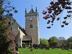 A bright spring day on a country churchyard, surrounded by mature trees. The church nave is on the extreme left, and at the far end is tall, square, tower capped by a pointed wooden roof, not quite a spire, and with pinacles on all 4 corners. A bold white clockface is on the tower. The church has an ope porch, with pillars of wood. Dark, old, gravestones are scattered in the green grass.