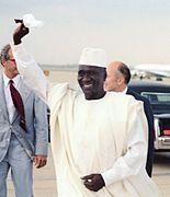 bystfoto av en man klädd i en boubou och en vit mössa, viftande med sin hand, på en asfalterad flygplats