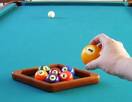 Racking up a game of seven-ball using the diamond rack more commonly used for nine-ball, but sideways. The 1 ball is about to be placed on the foot spot to complete the rack. Seven-ball diamond rack 1a.jpg