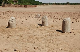 The remains of five stone columns emerging from an expanse of sand.