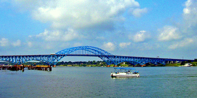 Profile of South Grand Island Bridge. Two sky-blue steel spans cross the river in five arches. The central arch alone is above the roadway, permitting passage of large freight ships.