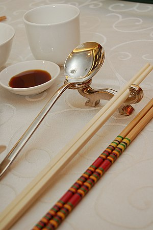 Customs and etiquette in Chinese dining - Photo showing serving chopsticks (gongkuai) on the far right, personal chopsticks (putongkuai) in the middle, and a spoon. Serving chopsticks are usually more ornate than the personal ones.