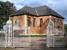 Small brick Neoclassical chapel behind ornate iron gates